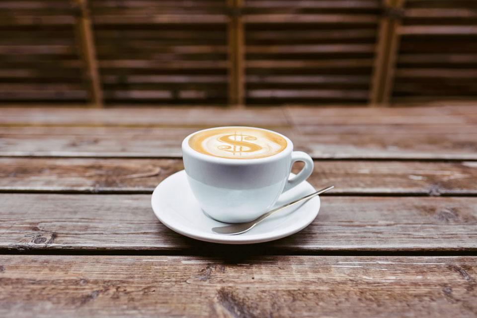 Latte with a dollar sign written in the foam