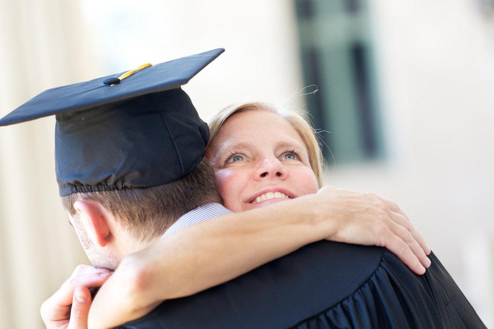 Mother hugging son at graduation