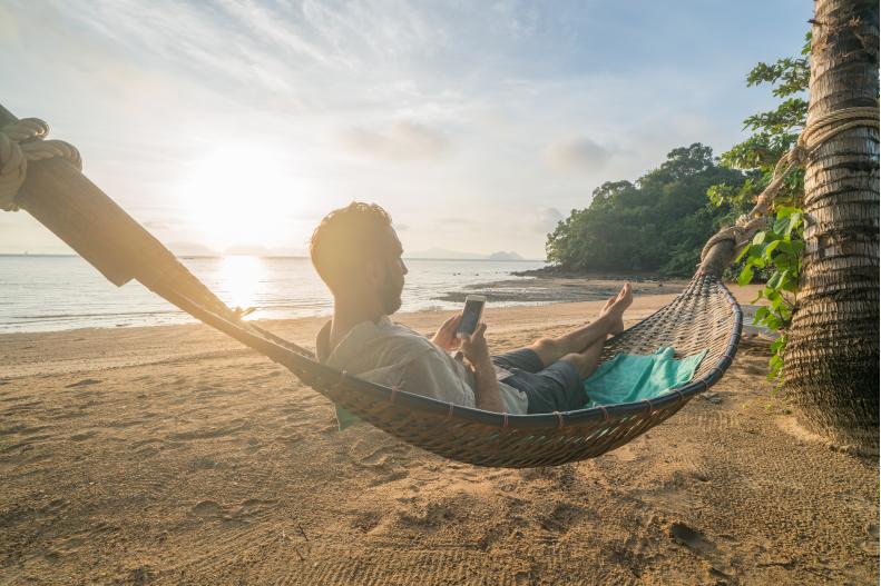 a person sitting in a hammock on a beach