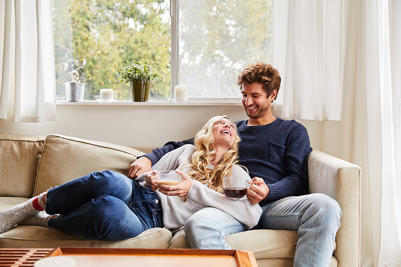 Happy young couple sitting on couch