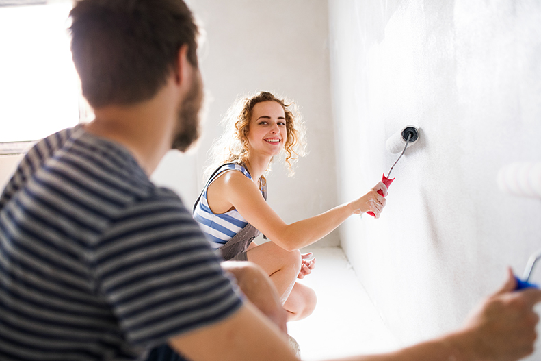Couple smiling and painting wall together